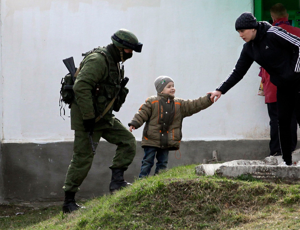 . A Russian soldier on patrol passes by a child playing with his mother in front of the Ukraine\'s infantry base in Perevalne, Ukraine, Tuesday, March 4, 2014.  (AP Photo/Darko Vojinovic)