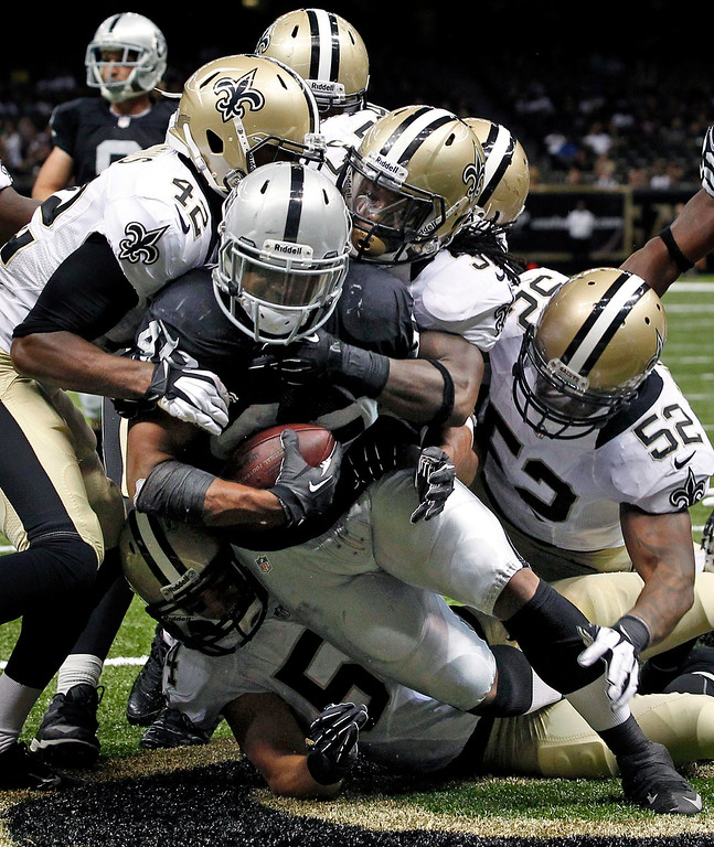 . Oakland Raiders running back Jamize Olawale (49) is tackled for a safety by New Orleans Saints free safety Isa Abdul-Quddus (42), defensive back Jerico Nelson, center, inside linebacker Kevin Reddick (52) and outside linebacker Will Herring, bottom, in the second half of an NFL preseason football game at the Mercedes-Benz Superdome in New Orleans, Friday, Aug. 16, 2013. (AP Photo/Jonathan Bachman)