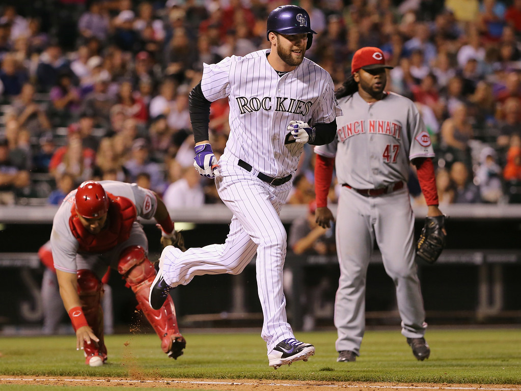 . DENVER, CO - AUGUST 15:  Jordan Lyles #24 of the Colorado Rockies hits a pinch hit sacrifice bunt as catcher Brayan Pena #29 of the Cincinnati Reds fields the ball and pitcher Johnny Cueto #47 of the Cincinnati Reds backs up the play in the fifth inning at Coors Field on August 15, 2014 in Denver, Colorado.  (Photo by Doug Pensinger/Getty Images)