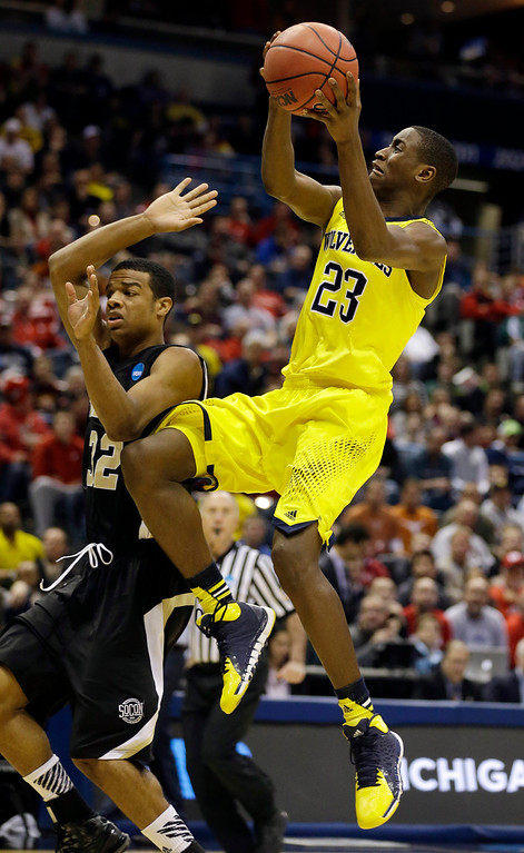 . Michigan guard Caris LeVert (23) drives to the basket over Wofford guard Spencer Collins (32) during the second half of a second round NCAA college basketball tournament game Thursday, March 20, 2014, in Milwaukee. (AP Photo/Jeffrey Phelps)
