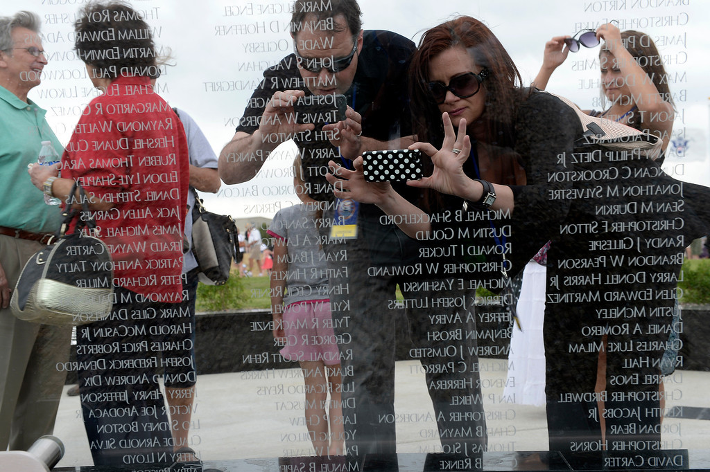 . Lisa Hoskinson 39-years-old (R) takes a photo of her cousin\'s name Ryan Baum on the glass panel after the dedication May 26, 2013 in Aurora.  (Photo By John Leyba/The Denver Post)