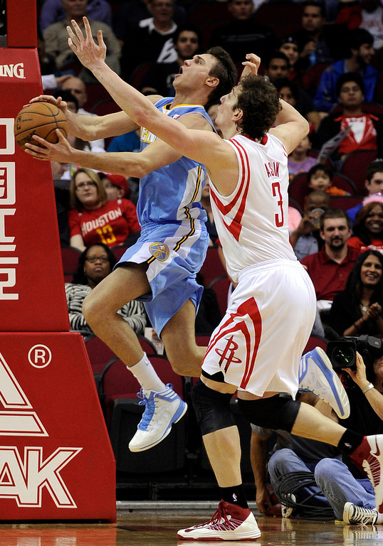 . Houston Rockets\' Omer Asik (3) pressures Denver Nuggets\' Danilo Gallinari, left, as he goes to the basket in the second half of an NBA basketball game Wednesday, Jan. 23, 2013, in Houston. Denver won 105-95. (AP Photo/Pat Sullivan)