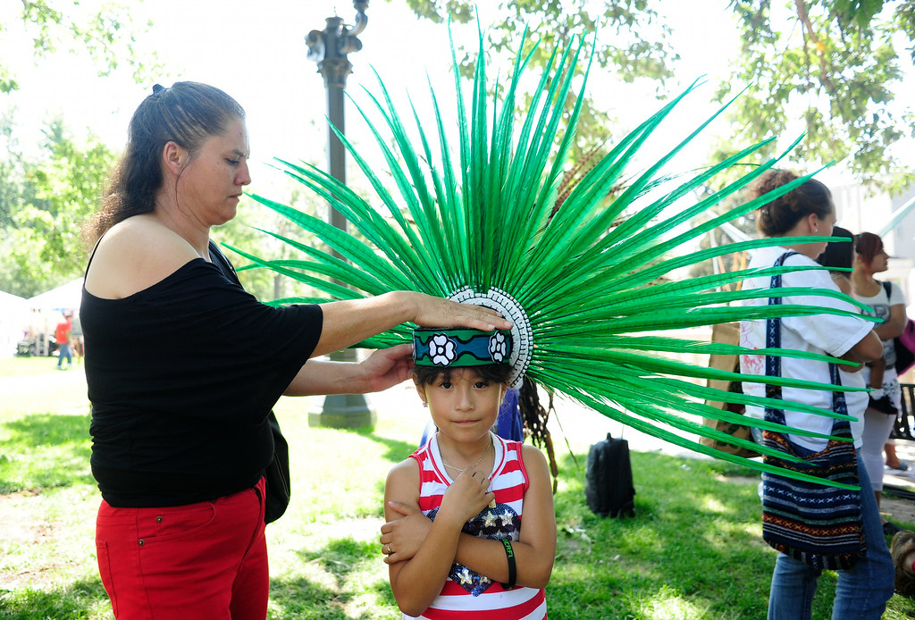 . Veronica Cabrera helps her granddaughter Ximena Trejo Cabrera, 7, get ready for her performance with the Huitzilopochtli Traditional Aztec Dance Group during the A Taste of Colorado festival at Civic Center Park in Denver, Colorado, Saturday, August 30, 2014. (Photo By Brenden Neville / Special to The Denver Post)