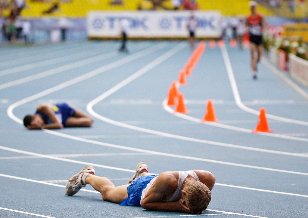 . Athletes lie on the track after the men\'s 20 kilometer race walk at the World Athletics Championships in the Luzhniki stadium in Moscow, Russia, Sunday, Aug. 11, 2013. (AP Photo/Anja Niedringhaus)