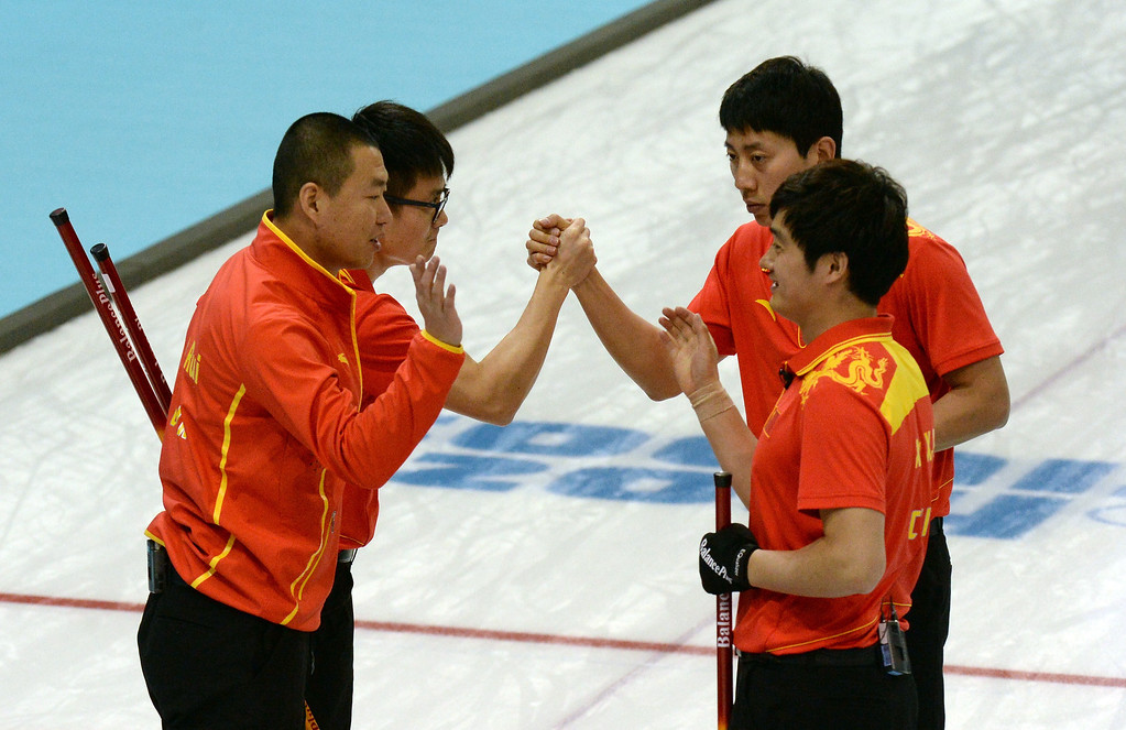 . China\'s curling team celebrates after winning the 2014 Sochi Winter Olympics Men\'s Curling Round Robin Session 12 match against Great Britain at the Ice Cube Curling Centre in Sochi on February 17, 2014.  YURI KADOBNOV/AFP/Getty Images