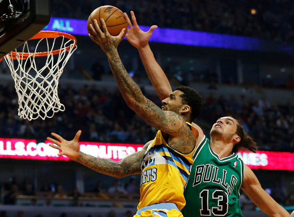 . Denver Nuggets\' Wilson Chandler (L) goes to the basket against Chicago Bulls\' Joakim Noah during the first half of their NBA basketball game in Chicago, Illinois March 18, 2013. REUTERS/Jim Young