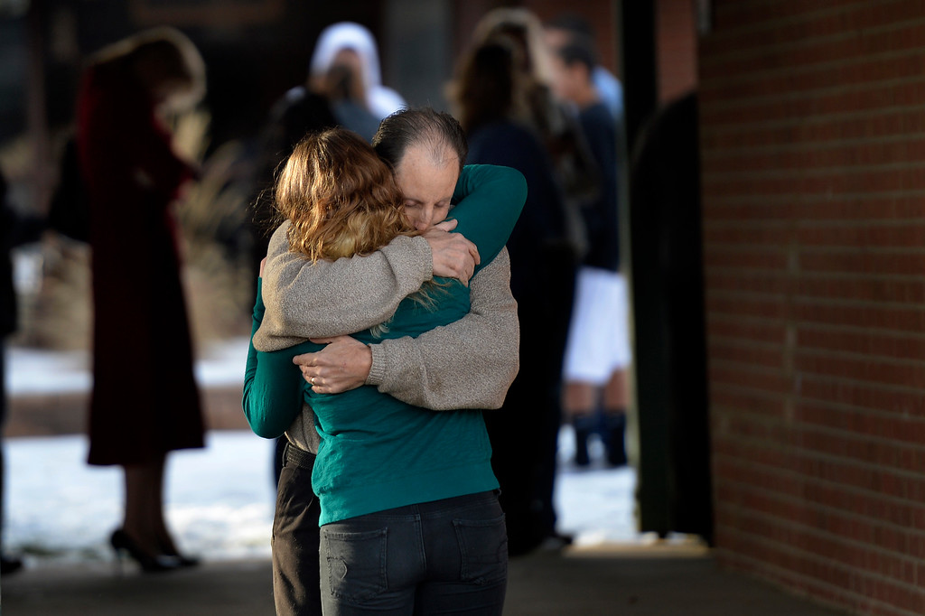 . CENTENNIAL, CO. - December 13: 16 year old junior Shayna is held tightly by her father Dave Keese as they leave Shepherd of the Hills church after she was released during a lockdown when a student carried a shotgun into Arapahoe High School and opened fire on Friday, wounding two fellow students before apparently killing himself December 13, 2013 Centennial, CO. (Photo By Joe Amon/The Denver Post)