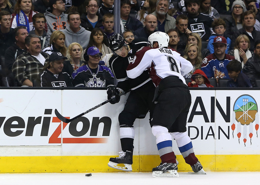 . LOS ANGELES, CA - NOVEMBER 23:  Jan Hejda #8 of the Colorado Avalanche checks Dustin Brown #23 of the Los Angeles Kings along the right wing boards in the second period of the NHL game at Staples Center on November 23, 2013 in Los Angeles, California.  (Photo by Victor Decolongon/Getty Images)