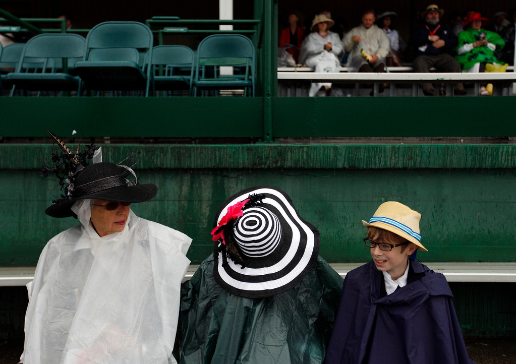 . From left, Donna Osborne, from Clemens, N.C., waits in the rain with Annie and Oz before the 139th Kentucky Derby at Churchill Downs Saturday, May 4, 2013, in Louisville, Ky. (AP Photo/David Goldman)