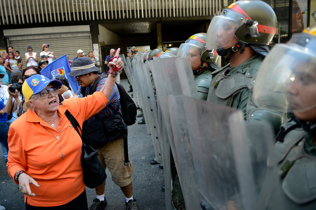 . An opposition activist gestures in front of a line of National Guards in riot gear during a protest demanding to know the real situation of President Hugo Chavez\'s health, in Caracas on March 3, 2013. Chavez is still in charge and mulling political, social and economic policies even as he receives a new round of chemotherapy, his vice president said Saturday. LEO RAMIREZ/AFP/Getty Images