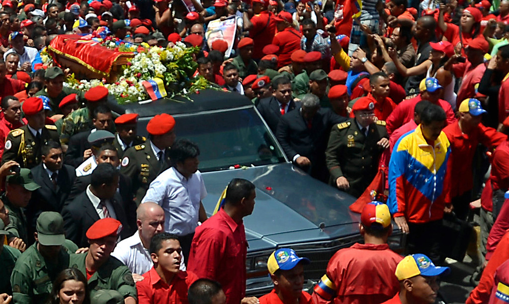 . Venezuelan acting President Nicolas Maduro (R) and Bolivian President Evo Morales (C in white) accompany the hearse carrying the coffin of Venezuelan President Hugo Chavez on its way to the Military Academy, on March 6, 2013, in Caracas.   AFP PHOTO/Juan BARRETO/AFP/Getty Images