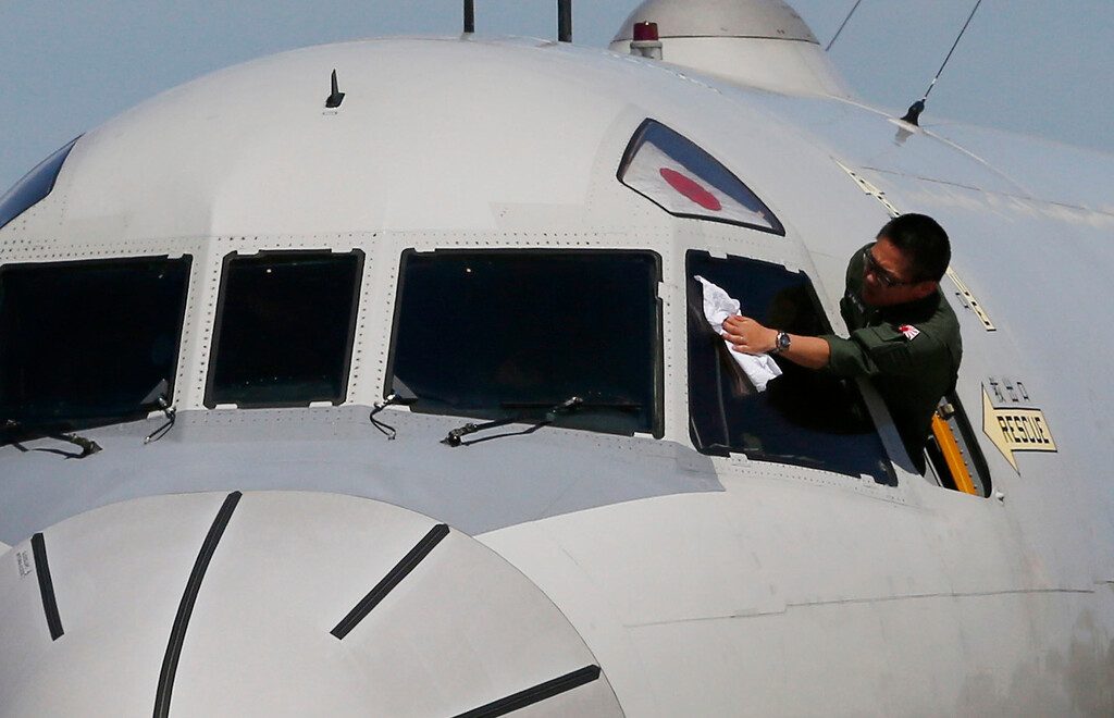 . A Japan Maritime Self-Defense Force Lockheed P-3C Orion aircraft crew member wipes clean the windshield of the aircraft before it takes off from the Royal Australian Air Force base Pearce to search for the missing Malaysia Airlines flight MH370, Monday, March 24, 2014 in Perth. (AP Photo/Jason Reed, Pool)