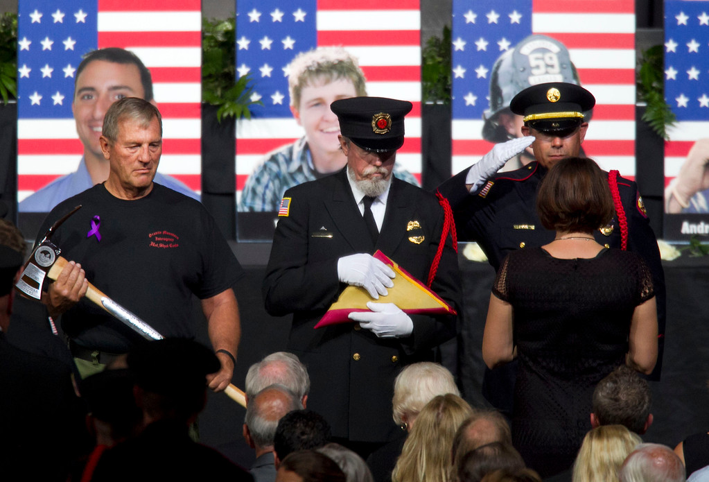 . A firefighter salutes a family member of one of the fallen firefighters after presenting her with the American flag as two other firefighters wait to present the Arizona flag and a pulaski during a memorial service for the 19 fallen firefighters at Tim\'s Toyota Center in Prescott Valley, Ariz. on Tuesday, July 9, 2013.     (AP Photo/The Arizona Republic, David Wallace, Pool)