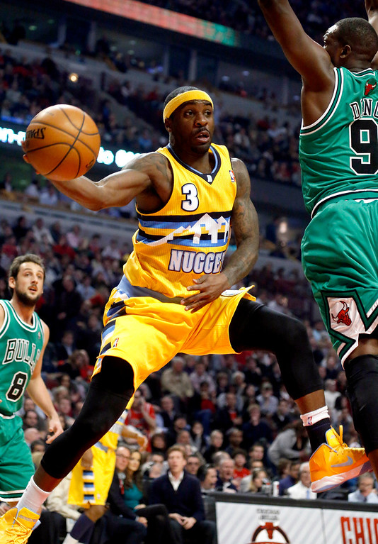 . Denver Nuggets guard Ty Lawson (3) passes the ball under pressure from Chicago Bulls forward Luol Deng (9) during the first half of an NBA basketball game, Monday, March 18, 2013, in Chicago. (AP Photo/Charles Rex Arbogast)