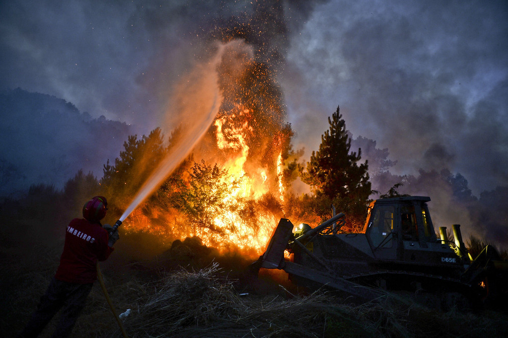 . A firefighter uses a hose as a bulldozer pushes earth onto a wildfire in Caramulo, central Portugal on August 29, 2013.  AFP PHOTO / PATRICIA DE MELO MOREIRA/AFP/Getty Images