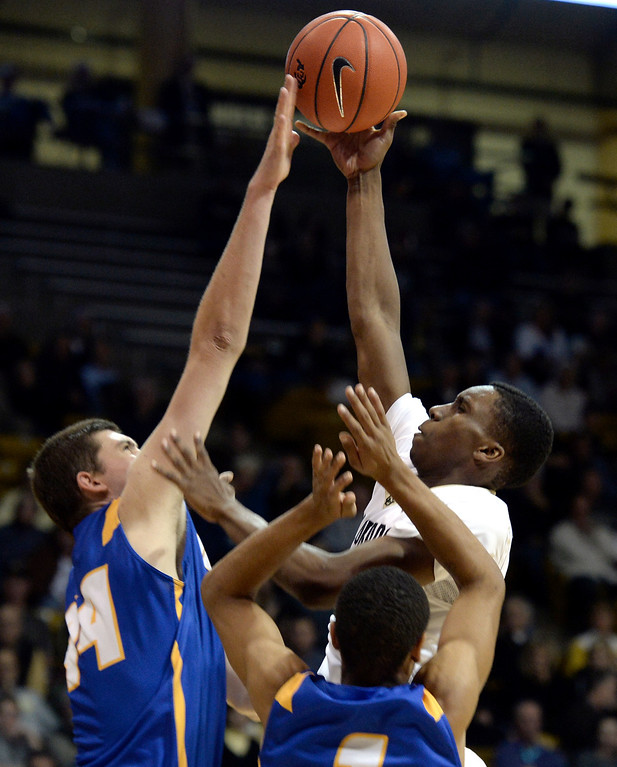 . University of Colorado\'s Jaron Hopkins takes a shot over the hands of Sam Beeler during a game against  the University of California Santa Barbara, on Nov. 20, at the Coors Event Center in Boulder. (Jeremy Papasso/Boulder Daily Camera)
