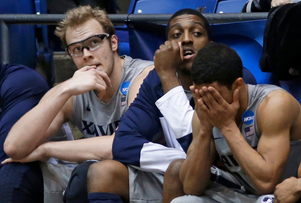 . Xavier players, left to right, Matt Stainbrook, James Farr, and Dee Davis sit on the bench in the closing minute of the team\'s 74-59 loss to North Carolina State in a first-round game of the NCAA college basketball tournament, Tuesday, March 18, 2014, in Dayton, Ohio. (AP Photo/Al Behrman)