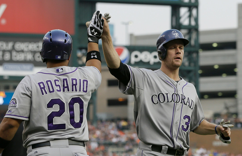 . Colorado Rockies first baseman Justin Morneau, right, is congratulated by teammate Wilin Rosario after scoring during the second inning of an interleague baseball game against the Detroit Tigers, Saturday, Aug. 2, 2014, in Detroit. (AP Photo/Carlos Osorio)
