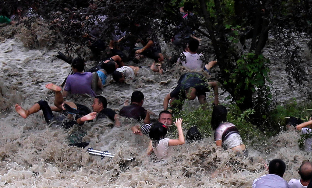 ". This picture taken on August 22, 2013 shows onlookers being washed away from huge waves from the ""Haining tide\"" - a daily occurrence when the river tides hit the banks of the city - as the waves surged higher than usual due to the influence of Typhoon Trami in the region in Haining, in eastern China\'s Zhejiang province.     AFP PHOTOSTR/AFP/Getty Images"