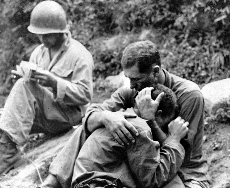 . An American infantryman, his buddy killed in action in the Korean War, weeps on the shoulder of another GI somewhere in Korea, Aug. 28, 1950.  Meanwhile, a corpsman, left, goes about the business of filling out casualty tags.  No identifications  available.  (AP Photo/Al Chang)