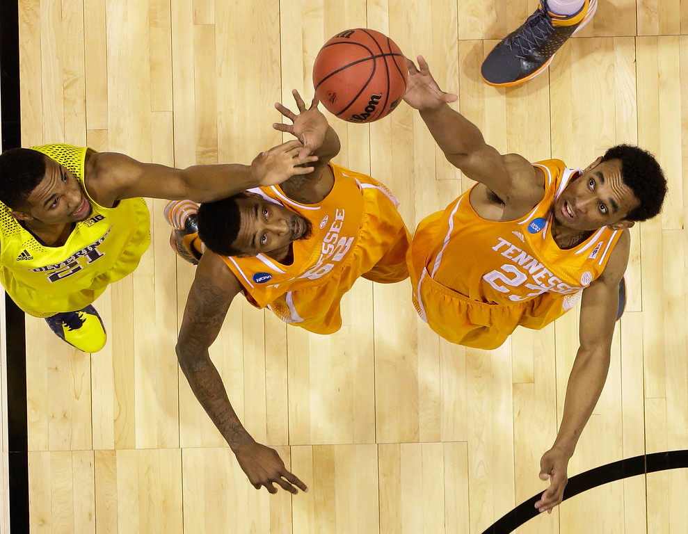 . Michigan\'s Zak Irvin (21) goes after a loose ball with Tennessee\'s Derek Reese (23) and Jordan McRae during the first half of an NCAA Midwest Regional semifinal college basketball tournament game Friday, March 28, 2014, in Indianapolis. (AP Photo/Michael Conroy)