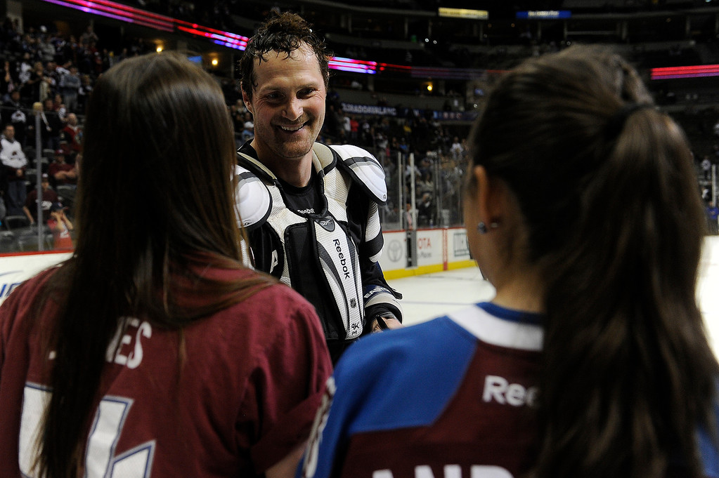. Milan Hejduk (23) of the Colorado Avalanche signs his jersey for a fan during the Sweaters Off Our Backs promotion following the third period on Saturday, April 27, 2012 at Pepsi Center. Seth A. McConnell, The Denver Post