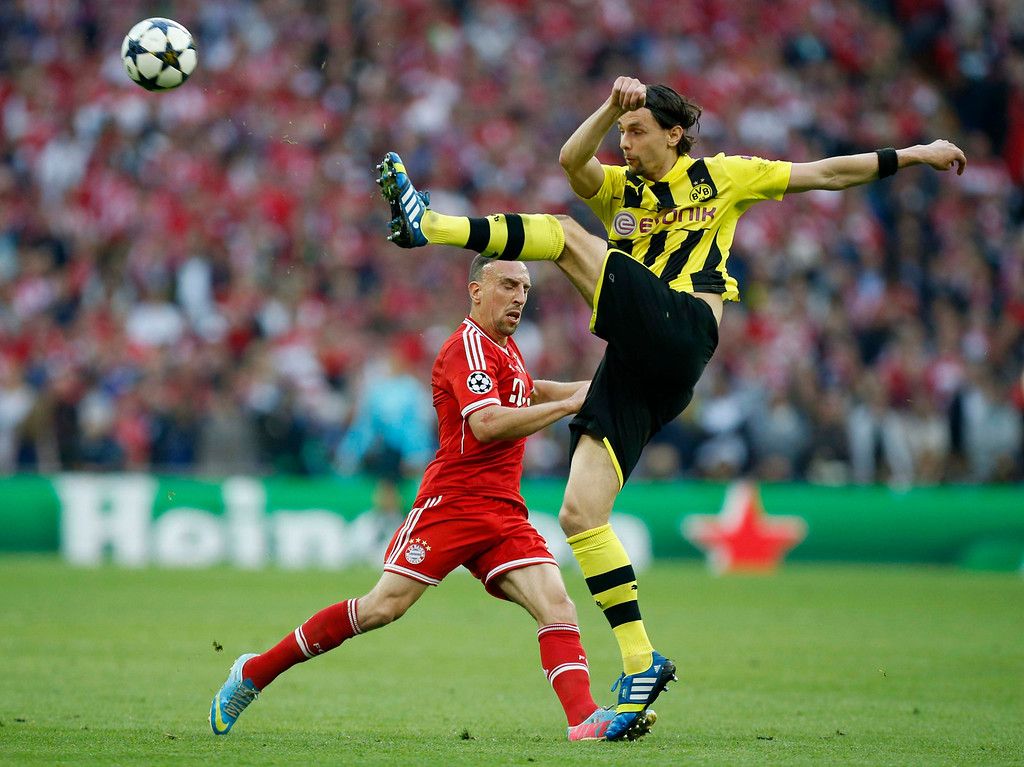 . Bayern\'s Franck Ribery of France, background, vies for the ball with Dortmund\'s Neven Subotic of Serbia, during the Champions League Final between  Borussia Dortmund and Bayern Munich, at Wembley Stadium in London, Saturday May 25, 2013. (AP Photo/Jon Super)