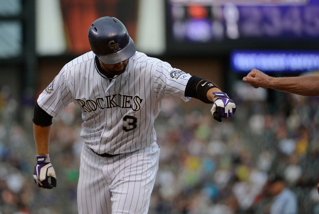 . DENVER, CO - JUNE 27: Colorado Rockies right fielder, Michael Cuddyer gets a fist pump from first base coach, Rene Lachemann after Cuddyer hit an RBI single in the first inning against the San Francisco Giants at Coors Field Saturday afternoon, June 29, 2013. (Photo By Andy Cross/The Denver Post)