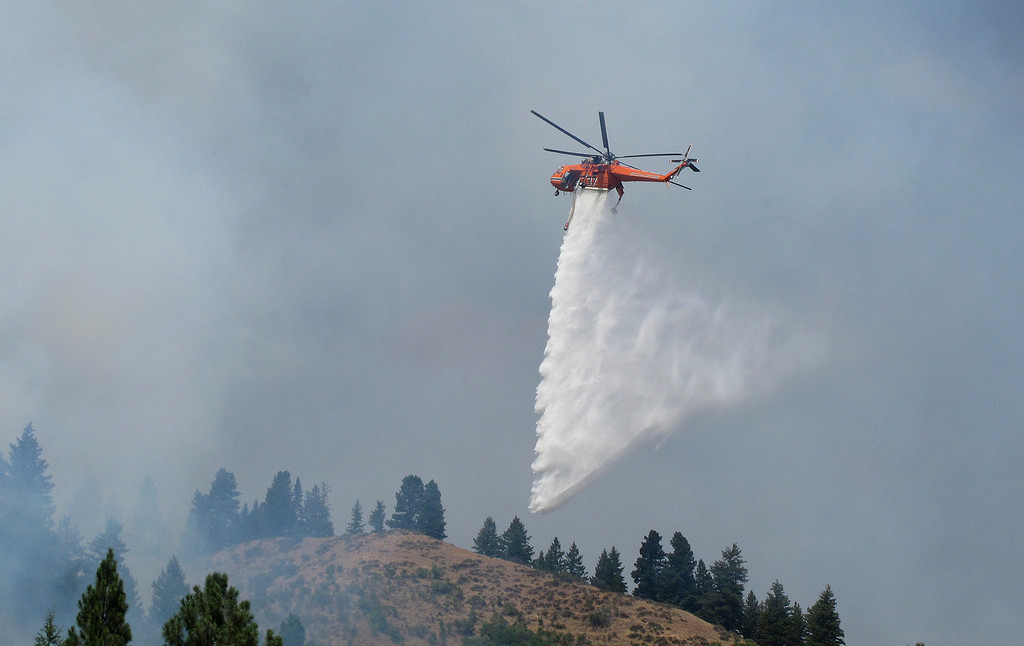. A firefighting helicopter drops water on the Elk Complex Fire in Pine, Idaho, which by Monday, Aug. 12, 2013 had burned through nearly 125 square miles of sage, grass and ponderosa pine forests. (AP Photo/John Miller)