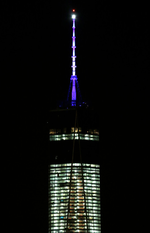 . In this Nov. 8, 2013 file photo, the beacon and spire of 1 World Trade Center are lit up, as seen from The Heights neighborhood of Jersey City, N.J.   (AP Photo/Julio Cortez, File)