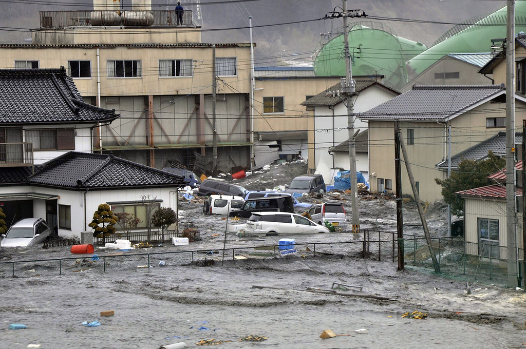 . A tsunami, tidal wave smashes vehicles and houses at Kesennuma city in Miyagi prefecture, northern Japan on March 11, 2011. A massive 8.9-magnitude earthquake shook Japan, unleashing a powerful tsunami that sent ships crashing into the shore and carried cars through the streets of coastal towns. (STR/AFP/Getty Images)