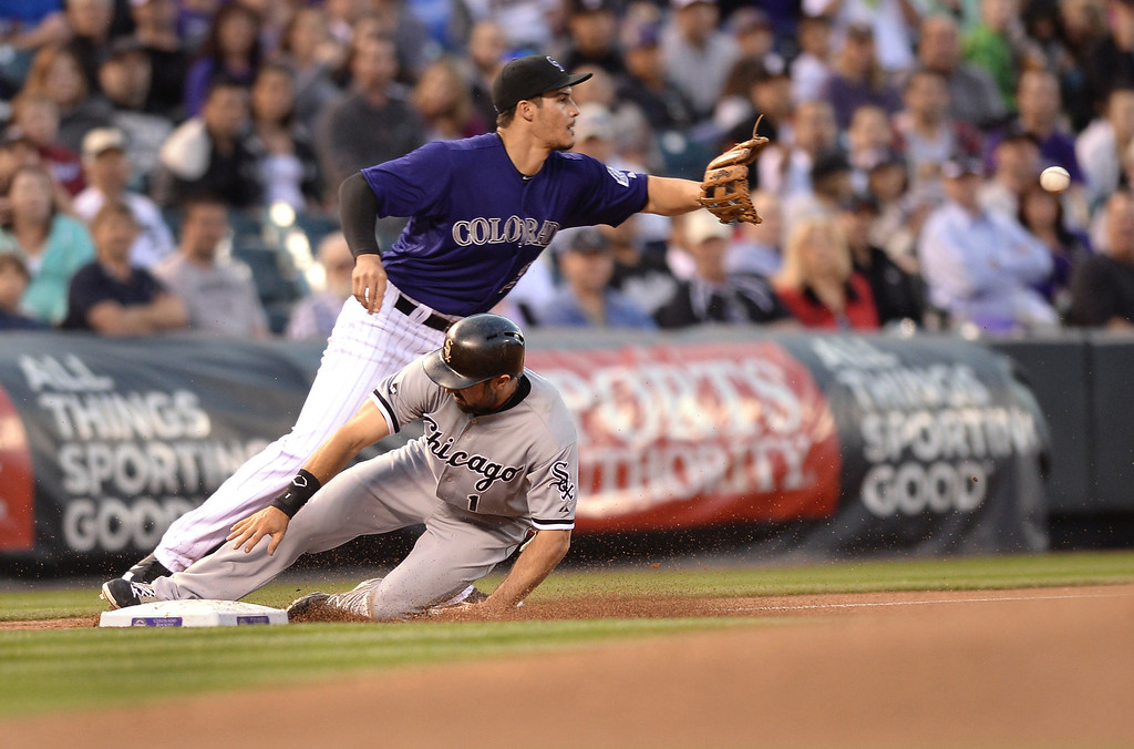. Chicago baserunner Adam Eaton slid safely into third base as Colorado infielder Nolan Arenado took the throw and made a play at second base to retire Marcus Semien in the third inning as the Colorado Rockies hosted the Chicago White Sox on Tuesday, April 8, 2014.    (Photo by Karl Gehring/The Denver Post)