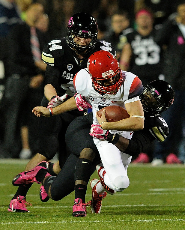 . BOULDER, CO. - OCTOBER 26: Colorado lineman De\'Jon Wilson (90) brought down Arizona quarterback B.J. Denker  (7) in the first half. The University of Colorado football team hosted Arizona Saturday night, October 26, 2013. Photo By Karl Gehring/The Denver Post
