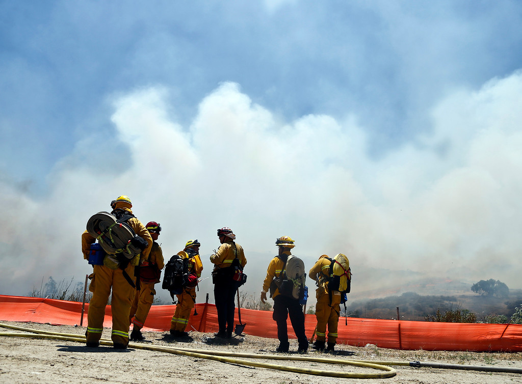 . Firefighters face a huge smoke cloud as they plan their attack on a wild fire Tuesday, May 13, 2014, in San Diego.  (AP Photo)