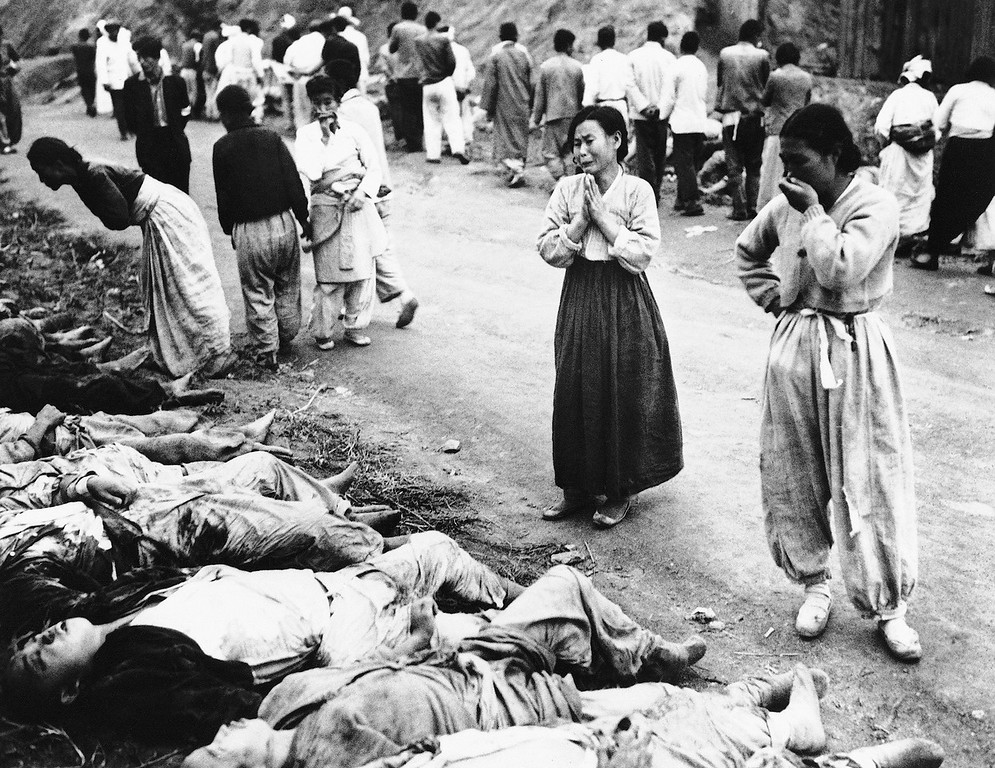 . Korean women weep as they identify bodies on Oct. 28, 1953. The army said the victims were among political prisoners killed by suffocation by the Communists outside Hambung, Korea. The Army said the victims were forced into caves which were then sealed off. (AP Photo)