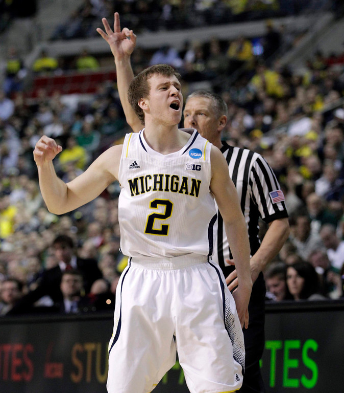 . Michigan Wolverines Spike Albrecht celebrates his three point shot against the VCU Rams during the second half of their third round NCAA tournament basketball game in Auburn Hills, Michigan March 23, 2013. REUTERS/Jeff Kowalsky