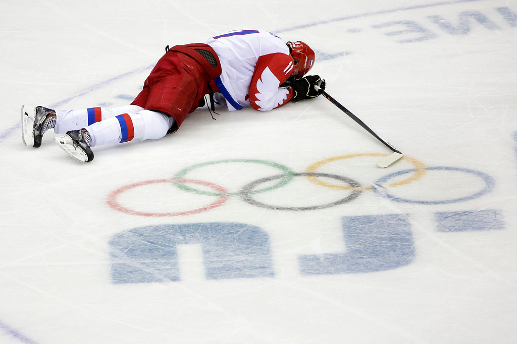 . Russia forward Yevgeni Malkin lies on the ice in the closing minutes of the third period in men\'s quarterfinal hockey game against Finland at Bolshoy Arena at the 2014 Winter Olympics, Wednesday, Feb. 19, 2014, in Sochi, Russia. Finland defeated Russia 3-1. (AP Photo/David J. Phillip )