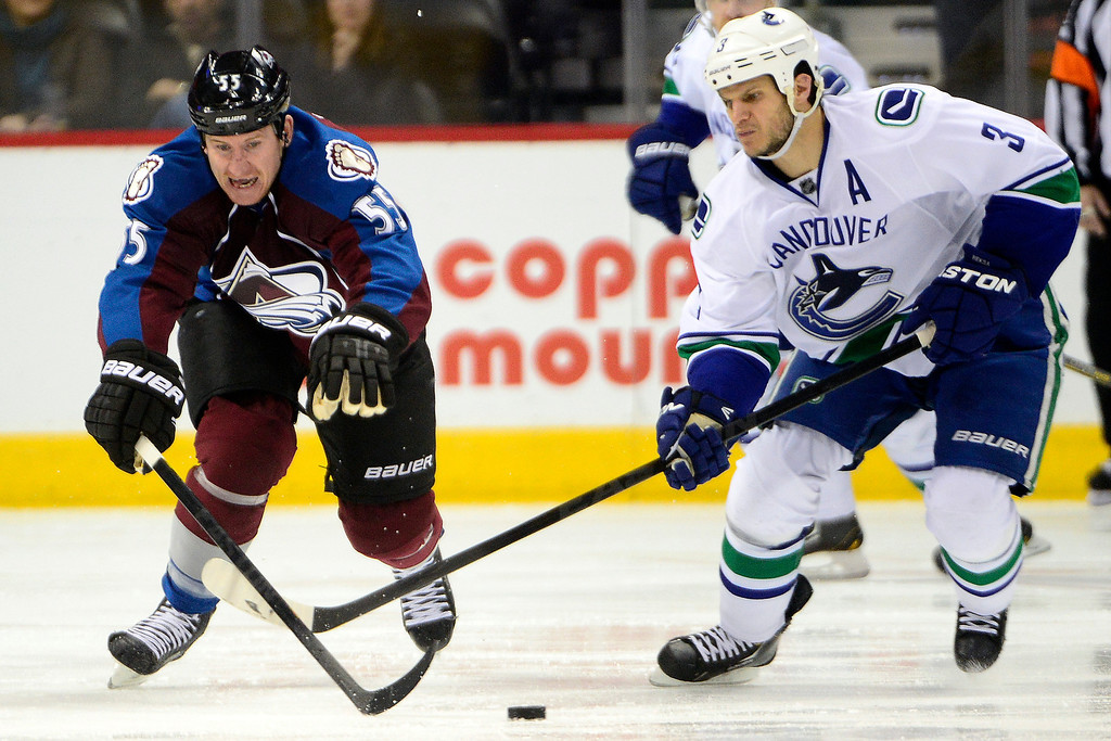 . DENVER, CO - MARCH 24: Cody McLeod (55) of the Colorado Avalanche and Kevin Bieksa (3) of the Vancouver Canucks race for the puck during the third period of action. The Colorado Avalanche lost to the Vancouver Canucks 3-2 at the Pepsi Center. (Photo by AAron Ontiveroz/The Denver Post)