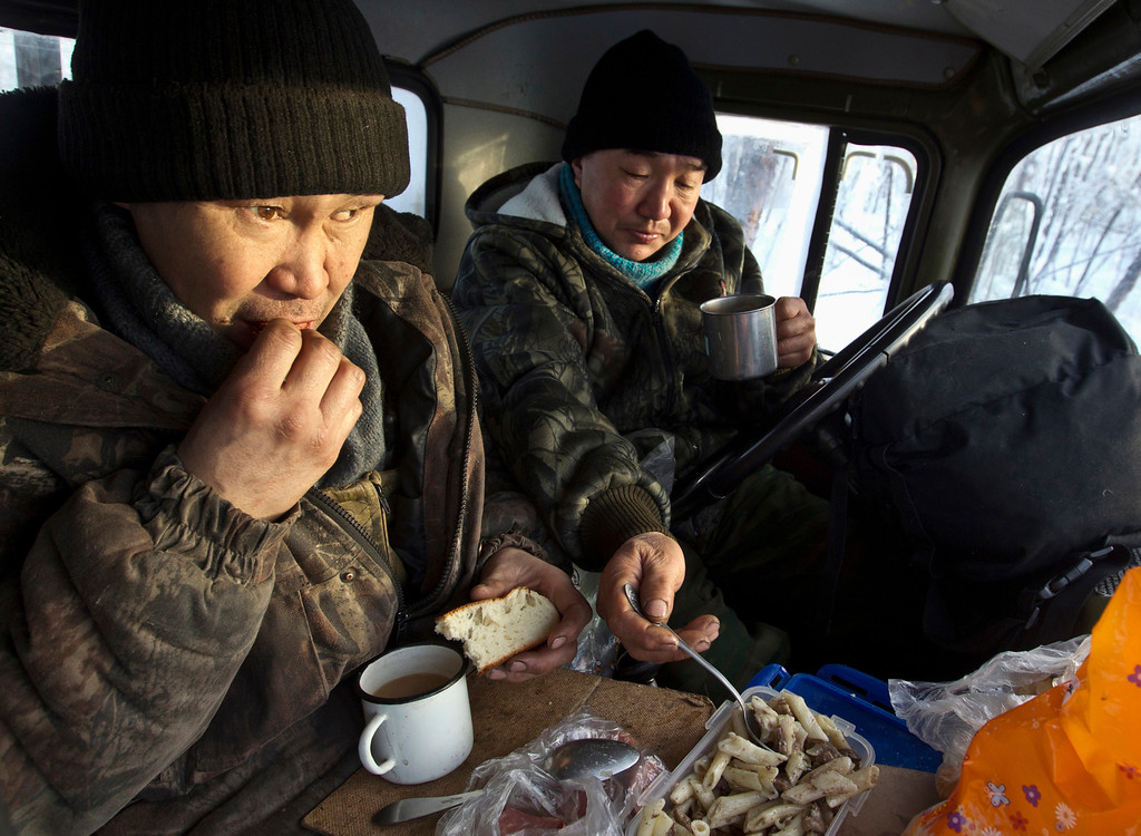 . Lumberjacks Alexey Egorov, 45, (L) and Semion VInokurov, 53, lunch in the cabin of their truck in forest outside Tomtor in the Oymyakon valley, in the Republic of Sakha, northeast Russia, January 29, 2013. The coldest temperatures in the northern hemisphere have been recorded in Sakha, the location of the Oymyakon valley, where according to the United Kingdom Met Office a temperature of -67.8 degrees Celsius (-90 degrees Fahrenheit) was registered in 1933. Yet despite the harsh climate, people live in the valley, and the area is equipped with schools, a post office, a bank, and even an airport runway (albeit open only in the summer).    Picture taken January 29, 2013.    REUTERS/Maxim Shemetov