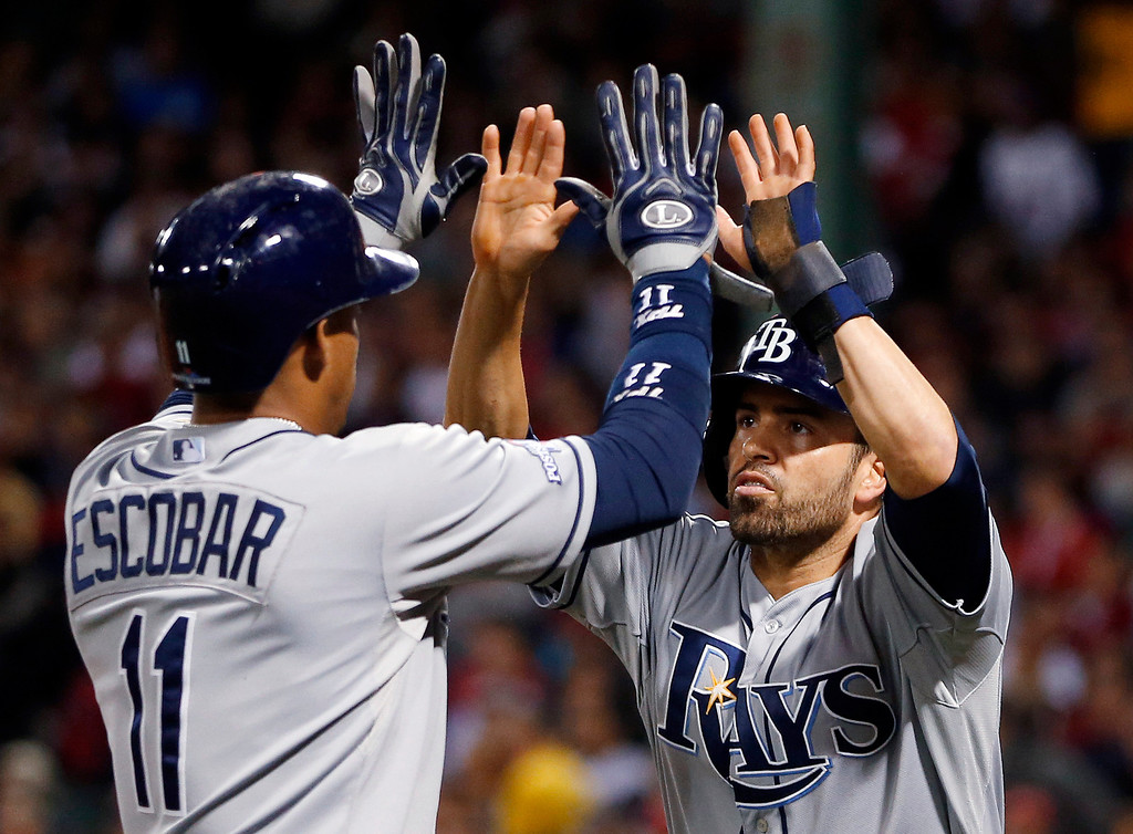 . Tampa Bay Rays\' Yunel Escobar, left, celebrates with David DeJesus after both scored on a double by James Loney in the fifth inning in Game 2 of baseball\'s American League division series against the Boston Red Sox on Saturday, Oct. 5, 2013, in Boston. (AP Photo/Michael Dwyer)