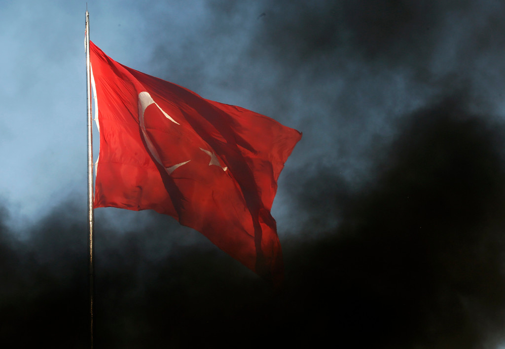 . A huge Turkish flag is obscured by black smoke from burning barricades during clashes between police and anti-government protesters in Istanbul\'s Taksim square June 11, 2013. REUTERS/Yannis Behrakis