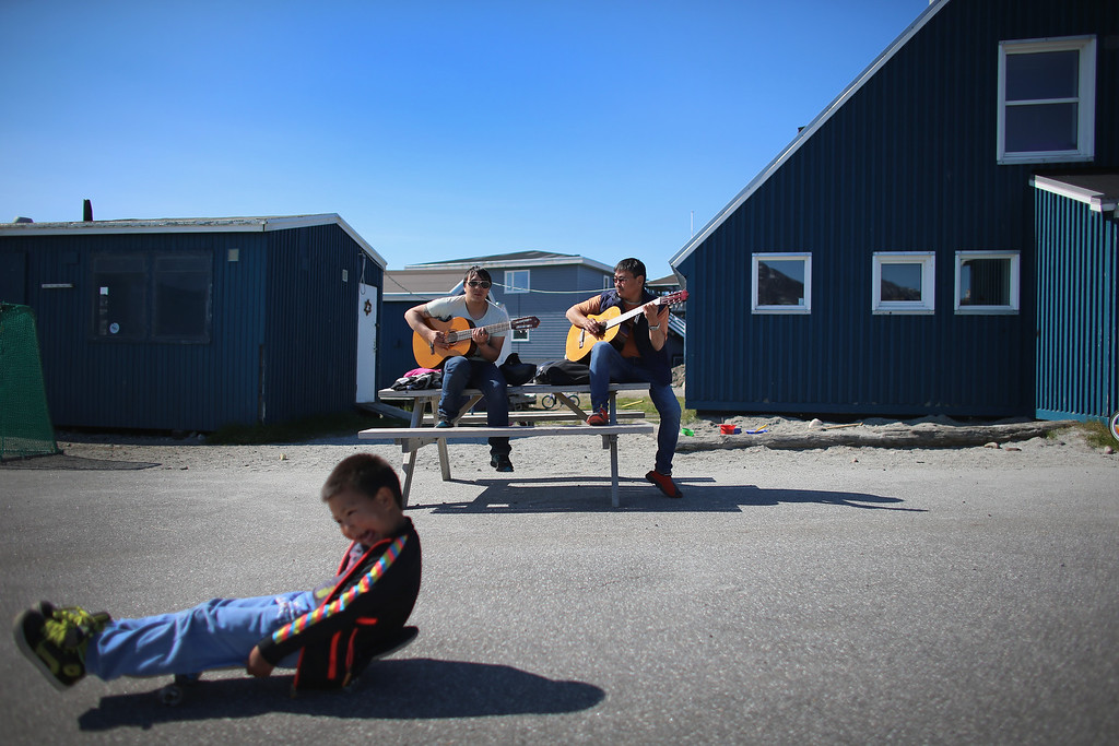 . Karl Peter Jakobsen (L) and Miki Lange practice with their guitars as they enjoy a warm summer day on July 29, 2013 in Nuuk, Greenland.  (Photo by Joe Raedle/Getty Images)