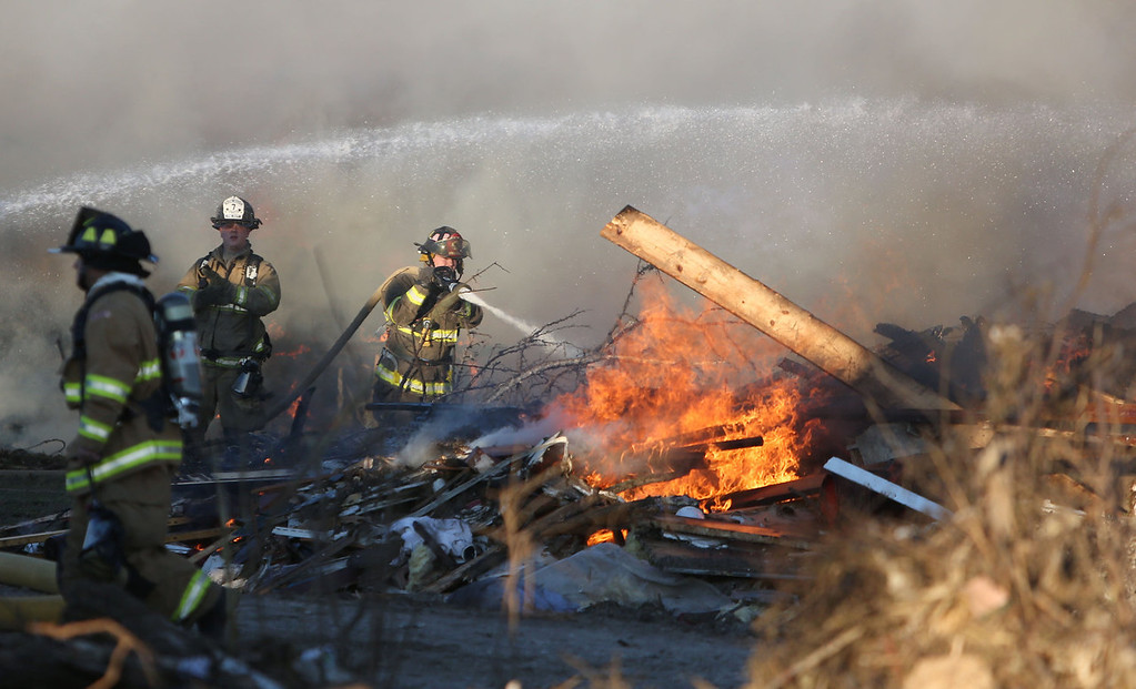 . Firefighters battle a rubbish fire in the aftermath of a tornado on November 18, 2013 in Washington, Illinois. A fast-moving storm system that produced several tornadoes that touched down across the Midwest left behind a path of destruction in 12 states. (Photo by Tasos Katopodis/Getty Images)