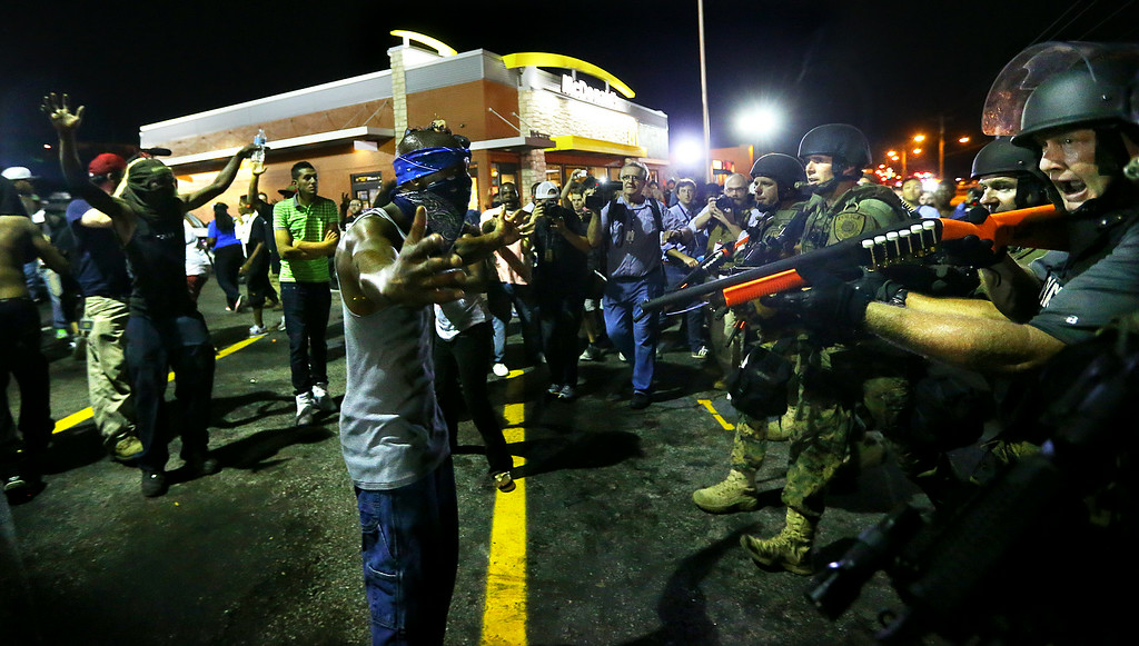 . Police officers move in to arrest protesters as they push and clear crowds out of the West Florissant Avenue area in Ferguson, Mo. early Wednesday, Aug. 20, 2014. On Aug. 9, 2014, a white police officer fatally shot Michael Brown, an unarmed black 18-year old, in the St. Louis suburb. (AP Photo/Atlanta Journal-Constitution, Curtis Compton)