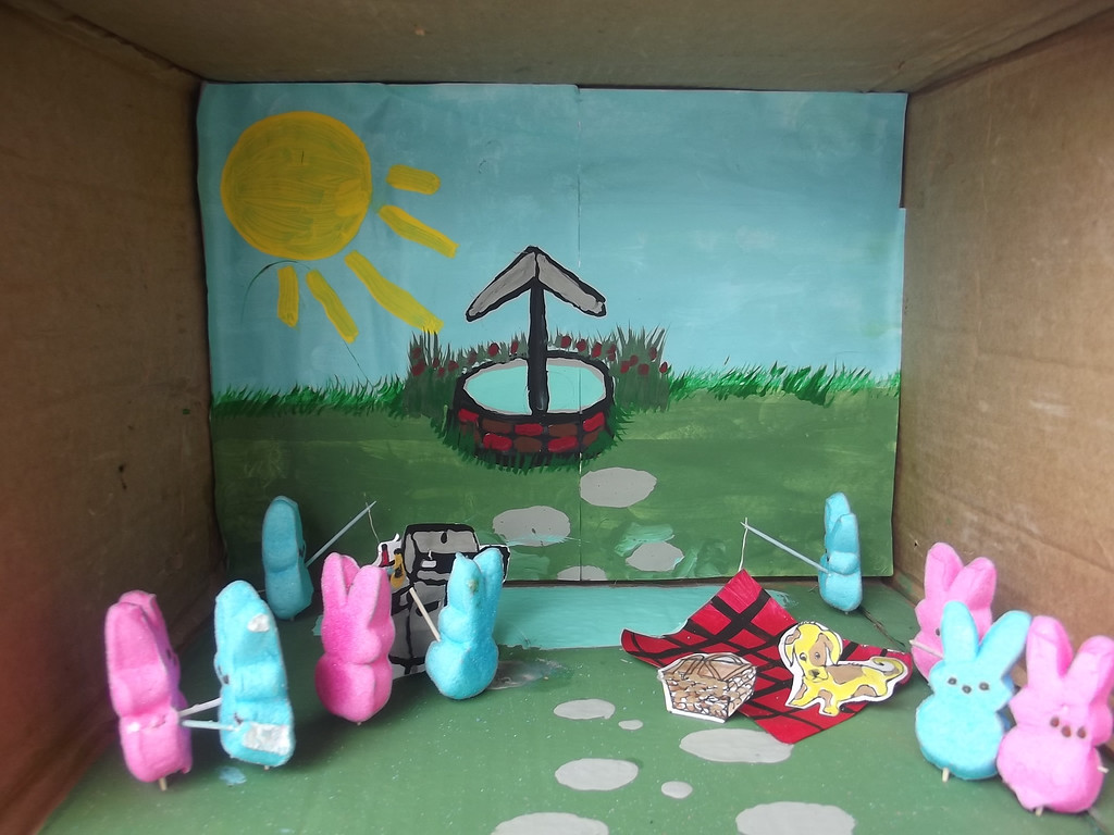 . In my Peep\'s diorama, the family is enjoying a barbecue in the park. Dad Peep is in charge at the barbecue pit. The youngest girl is sitting on a blanket and relaxing with her dog. The two boys are hanging out as they fish by the lake. The oldest girl and boy are having a chat. (Front and right). The married couple, (front and left), are dancing to festive spring music. The sun is shining bright and all is well, on this day, in Peepsville, USA. Grace Bowes