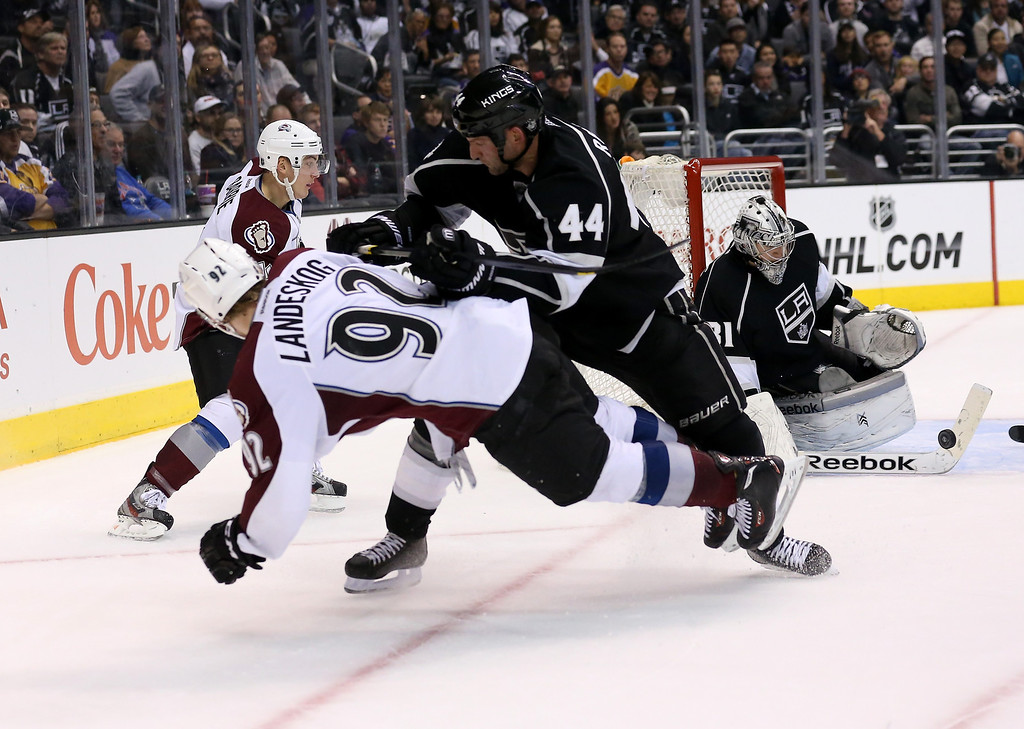 . LOS ANGELES, CA - DECEMBER 21:  Gabriel Landeskog #92 of the Colorado Avalanche is knocked to the ice by Robyn Regehr #44 of the Los Angeles Kings as goalie Martin Jones #31 stops Landeskog\'s shot at Staples Center on December 21, 2013 in Los Angeles, California.  The Kings won 3-2 on a shootout.  (Photo by Stephen Dunn/Getty Images)
