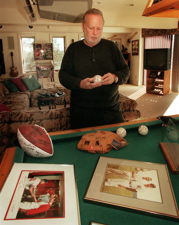 . Barry Fey and concert and sports memorabilia at Barry Fey\'s house for Mile High Stadium special section. On right foreground is picture of Fey when he was young and Joe DiMaggio. Fey holding an autographed ball a Signed glove and an autographed football from the Old timers game.  (Photo By Dave Buresh/The Denver Post)