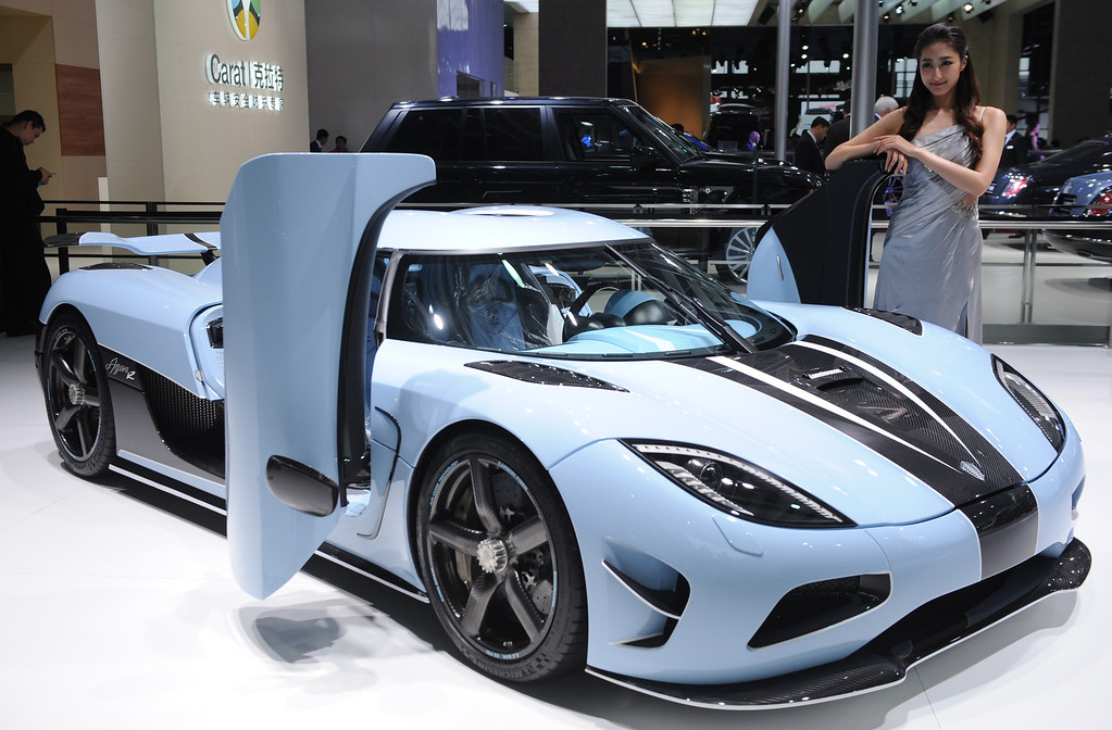 . This photo taken on April 20, 2013 shows a model posing next to a Koenigsegg sports car on display on media day at the Shanghai auto show. The Shanghai auto show, which opens to the public on April 21, is expected to attract more than 800,000 visitors over the course of nine days.     PETER PARKS/AFP/Getty Images