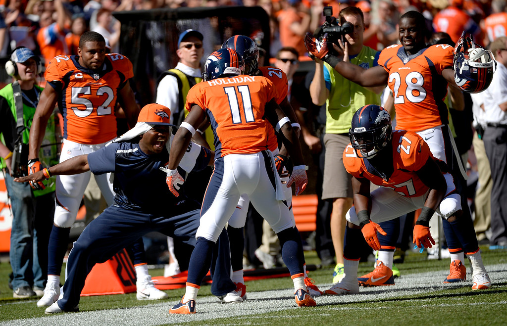 . Denver Broncos wide receiver Trindon Holliday (11) is greeted on the sidelines after running a kickoff back for a touchdown during the first quarter.  (Photo by Joe Amon/The Denver Post)