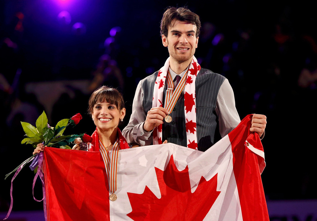 . Meagan Duhamel (L) and Eric Radford of Canada pose with their country\'s flag during the medal ceremony after placing third at the ISU World Figure Skating Championships in London, March 15, 2013.    REUTERS/Mark Blinch